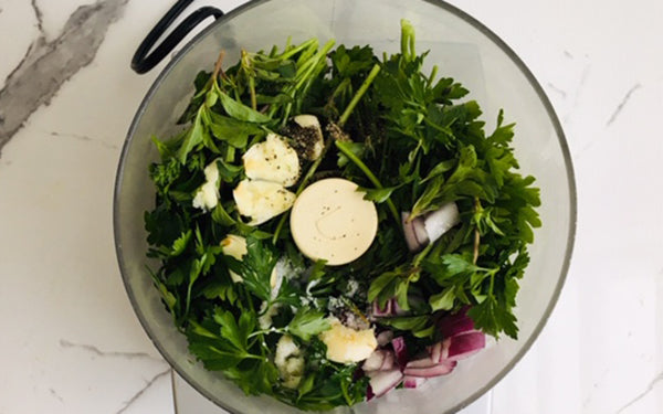 Add the parsley, oregano, black pepper, garlic, red onion, Fresno chili, lemon juice, and red wine vinegar to a food processor or blender, and pulse till chopped.