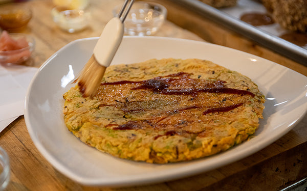 Transfer okonomiyaki onto plate. Drizzle with okonomiyaki sauce and mayonnaise. Sprinkle with ground bonito flakes, slivered ginger and cilantro or green onion. Cut into wedges and serve immediately.