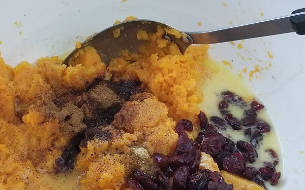 Transfer yams to a mixing bowl and mask to a smooth consistency. Then blend in the milk, 4 tablespoons of the butter, salt, vanilla, ginger, cinnamon, pepper, cranberries. To make ahead: stop here and refrigerate for up to 2 days.