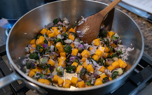 Heat the olive oil in a large sauté pan, and then add the shallots, butternut squash, and purple Brussels sprouts. Add a couple of pinches of sea salt and fresh ground black pepper, then stir and cook over medium-high heat for five minutes.