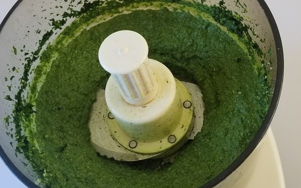 In a food processor, pulse spinach and pine nuts.