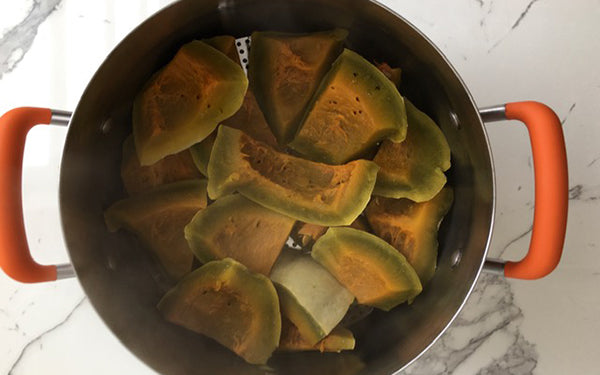 Place pumpkin pieces into a stock pot lined with a steamer basket and 2 inches of water, and bring water to a simmer, cover and steam for 1 hour. Remove pumpkin pieces to a large bowl and cool to room temperature.