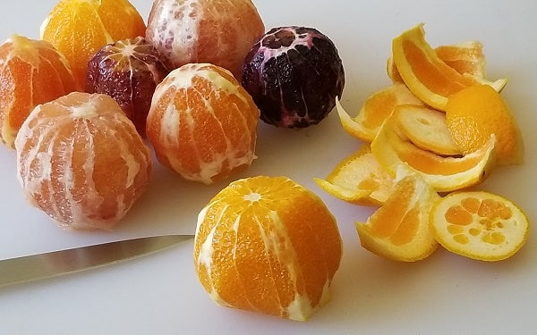 First, cut the bottom and top off of each citrus fruit. Stand the fruit up on its bottom and slice down the fruit skin, removing just enough to expose the fruit underneath.