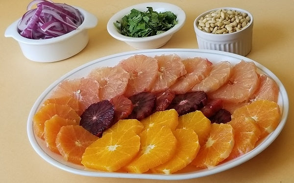 Arrange the slices on a platter and scatter the red onion, mint and pine nuts on top.