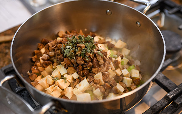 In a stockpot, heat the oil and add in the shallots, Asian pear, celery, celeriac, chestnuts, and sage and cook about 6 minutes. Add in the garlic and cook another minute.