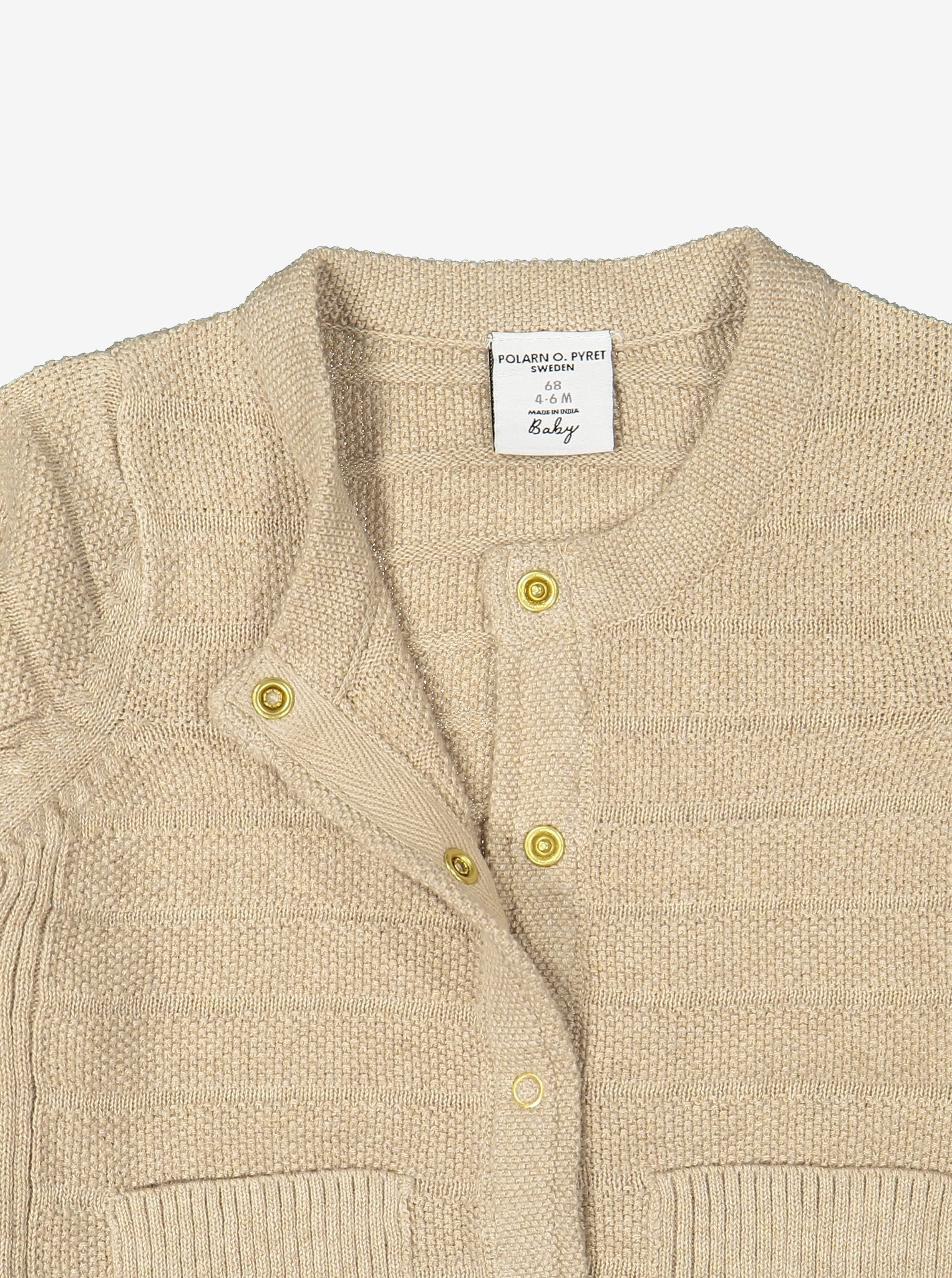 Close up of unisex beige knitted cardigan in 100% organic cotton showing easy popper fastening.