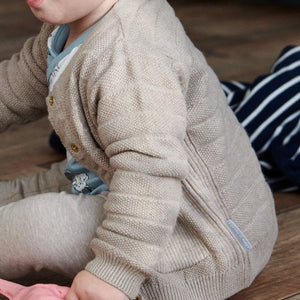 Close up of baby wearing unisex beige knitted cardigan paired with matching knitted trousers. Made in 100% organic cotton.