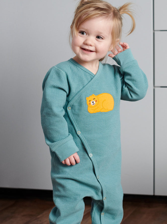 Toddler wearing wraparound onesie for newborn babies in GOTS organic cotton with adorable sleeping bear applique. With full length popper fastenings for speedy changes. Quality ribbed trim for added comfort.