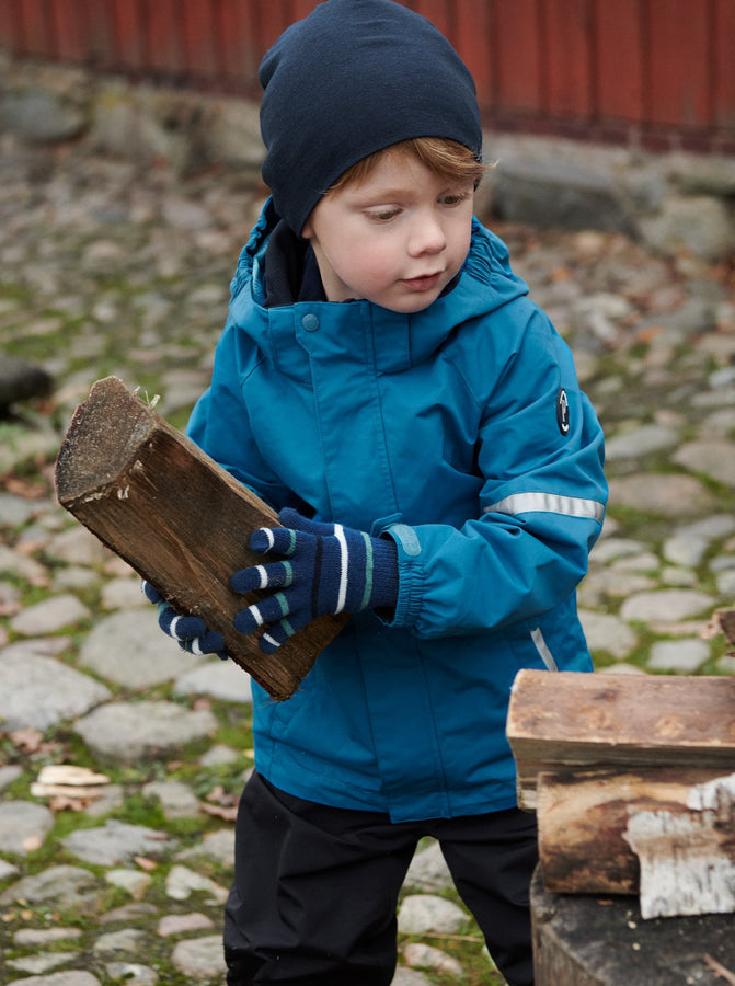 Boy playing outside wearing 100% waterproof kids coat in bright blue and 100% waterproof trousers in black. Accessories with warm merino wool beanie hat in navy
