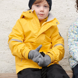 Boy sitting outside wearing 100% waterproof kids coat in bright yellow and 100% waterproof trousers in black. Accessories with warm merino wool beanie hat in navy