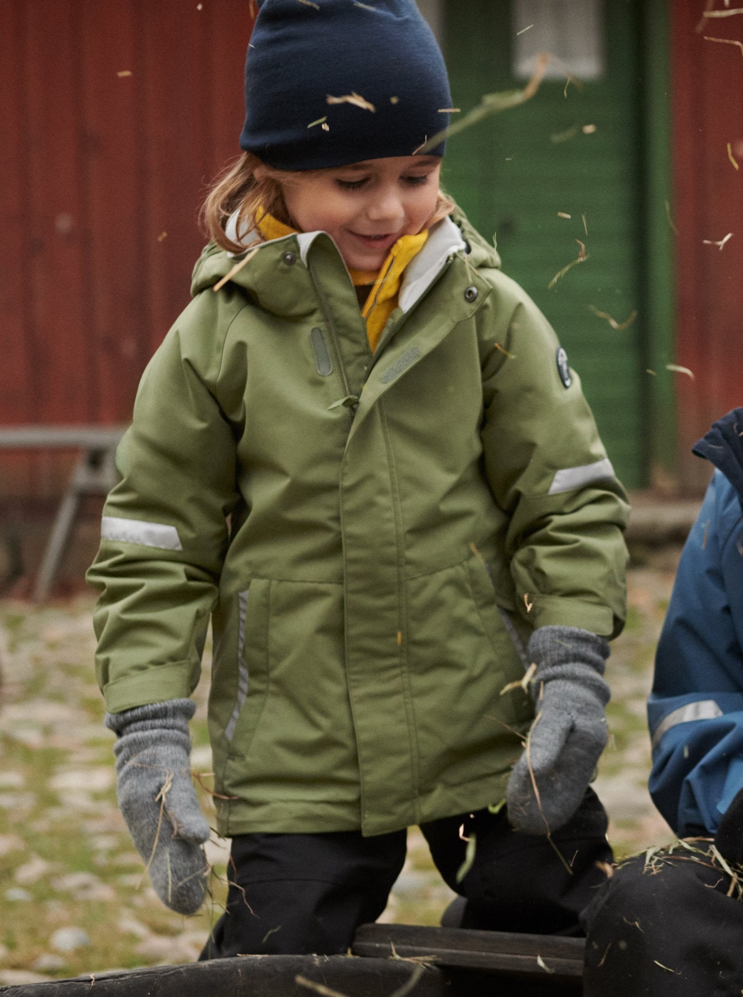 Girl playing outside wearing 100% waterproof kids coat in green and 100% waterproof trousers in black. Accessories with warm merino wool beanie hat in navy and grey wool gloves