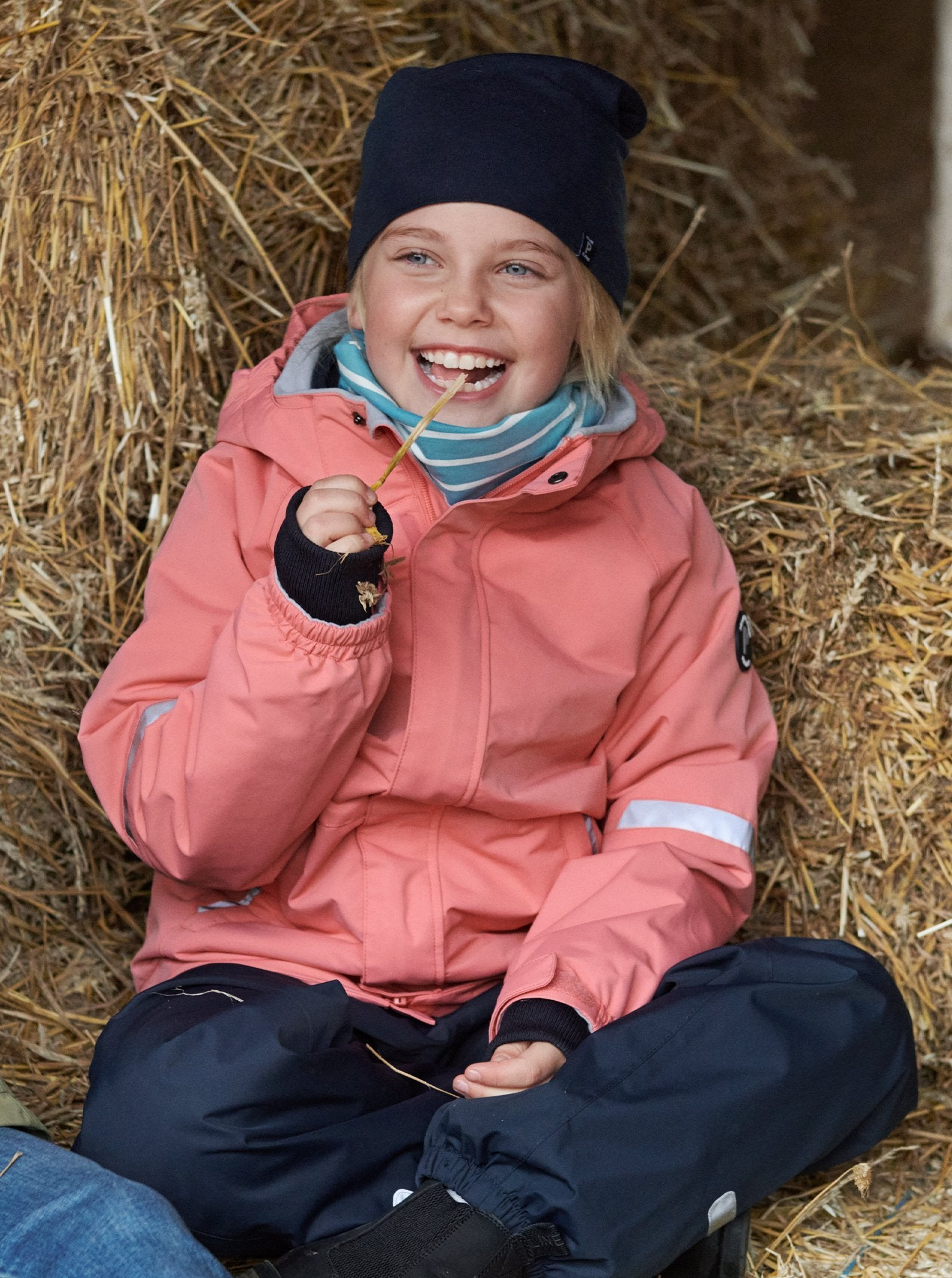 Girl sitting in hay barn wearing 100% waterproof kids coat in pink and 100% waterproof trousers in black. Accessories with warm merino wool beanie hat in navy and blue and white stripe organic cotton tube scarf