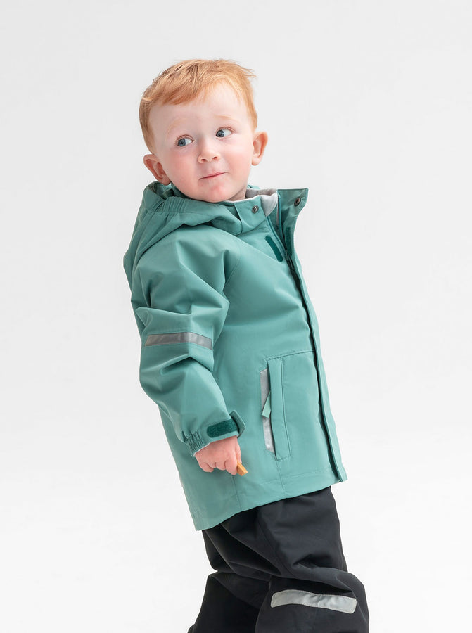 Kids waterproof shell jacket in colour green, with front pockets and detachable hood, made of lightweight and durable fabric.