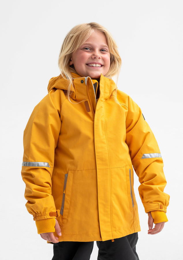 A young girl wearing a yellow waterproof jacket for kids, includes a detachable hood, front pockets and reflectors.
