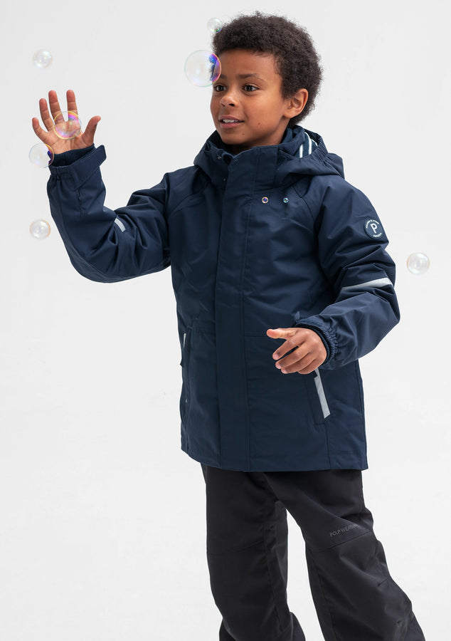 A little boy sporting a waterproof kids jacket in navy, with detachable hood and reflectors, made of soft shell fabric.