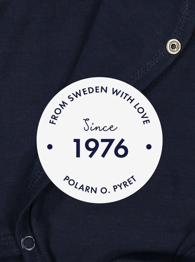 "White round label with the text 'From Sweden With Love, Since 1976"" shown in front of a navy blue babygrow background."