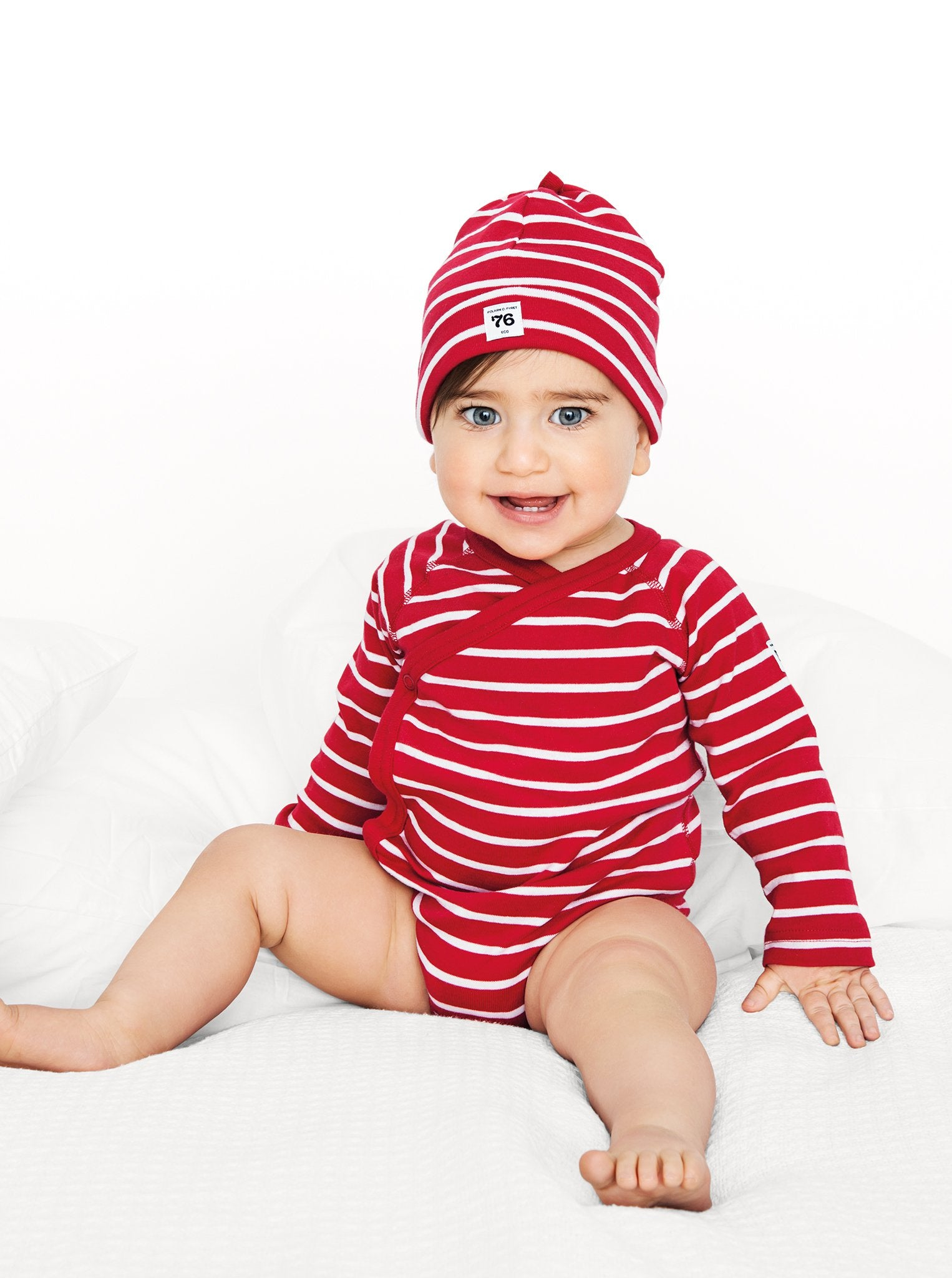 A toddler wearing a red and white striped cotton long sleeve babygrow, paired with a cotton hat in the same print