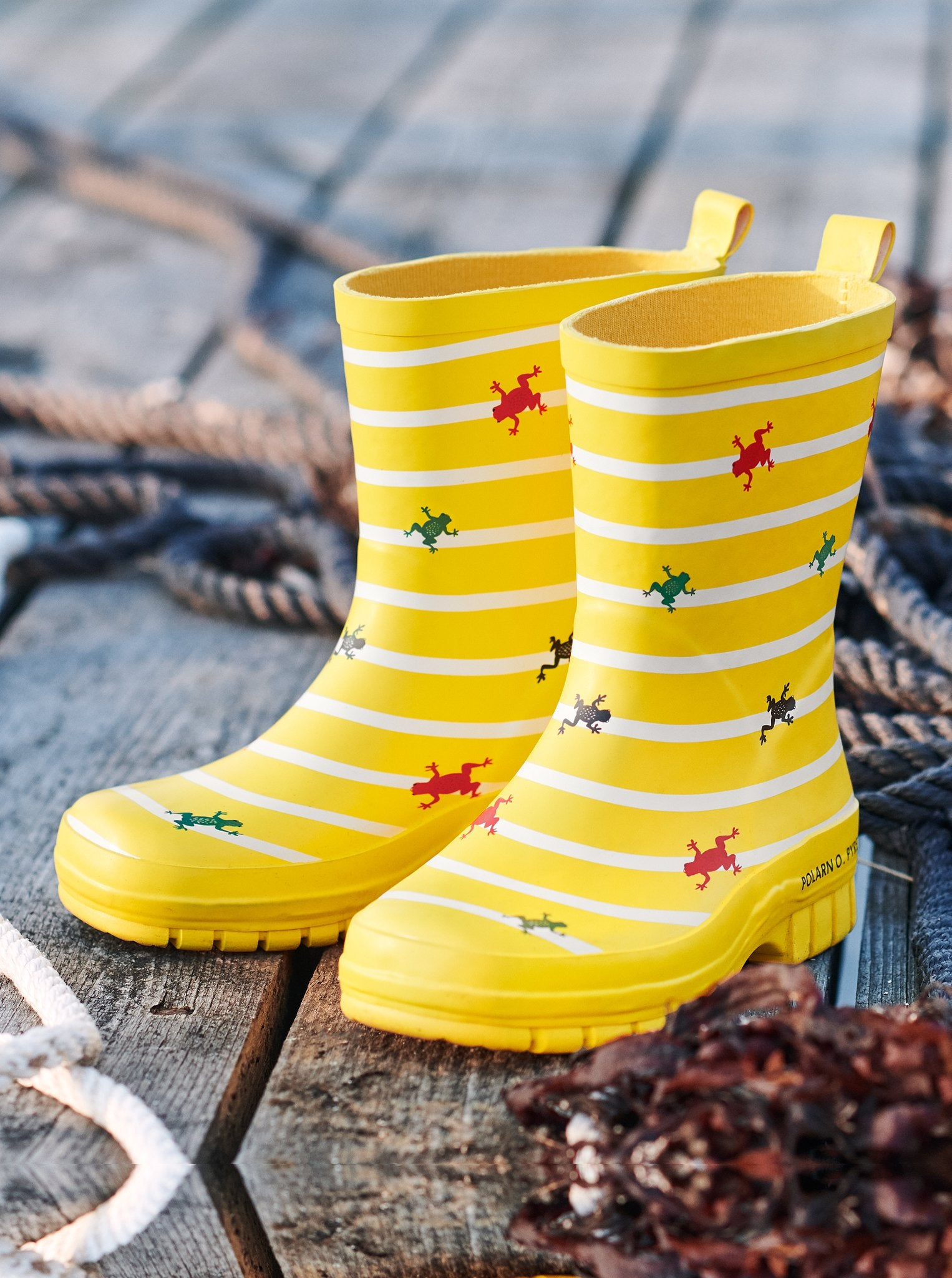 Yellow kids boots with cute frog & stripes design for rainy season, made with natural rubber and cotton for the inner lining.