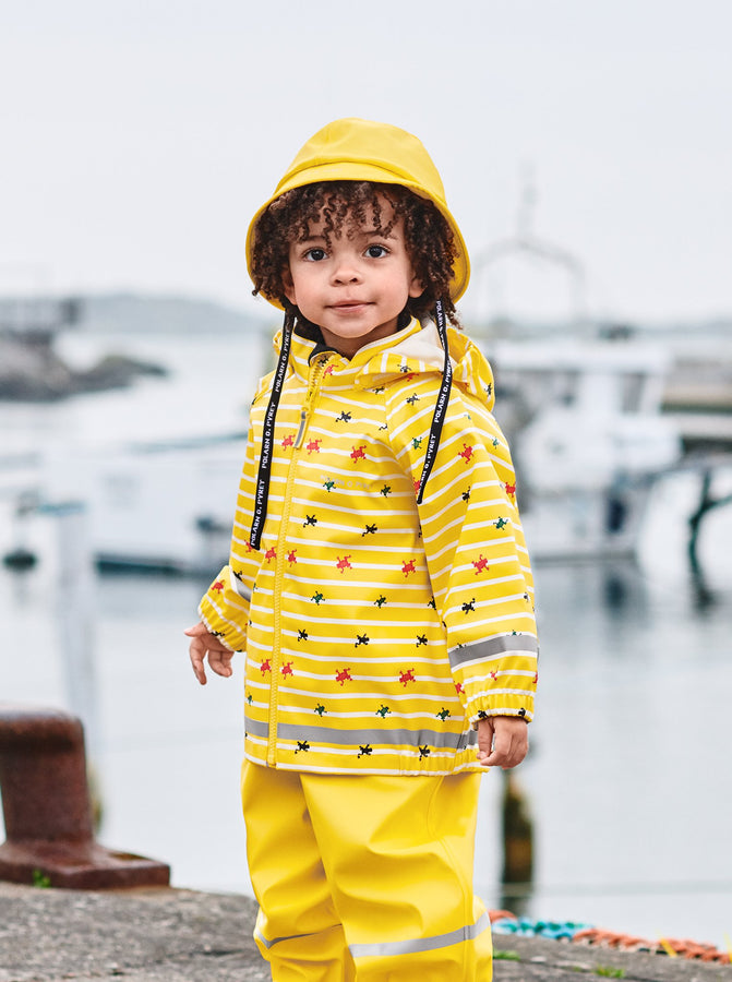 A little boy sporting a yellow raincoat for kids with frog & stripes pattern, paired with kids rain trousers and bucket hat.