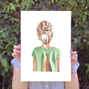 Image of person holding up large print of back of girls head in a bun and wearing a green top.