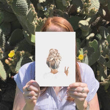 Load image into Gallery viewer, Image of girl holding A4 print of messy top knot peace girl with cactus in the background.