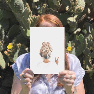 Image of girl holding A4 print of messy top knot peace girl with cactus in the background.