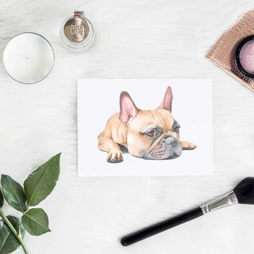Image of print of french bulldog with makeup, candle and leaf lying on a fluffy white blanket.