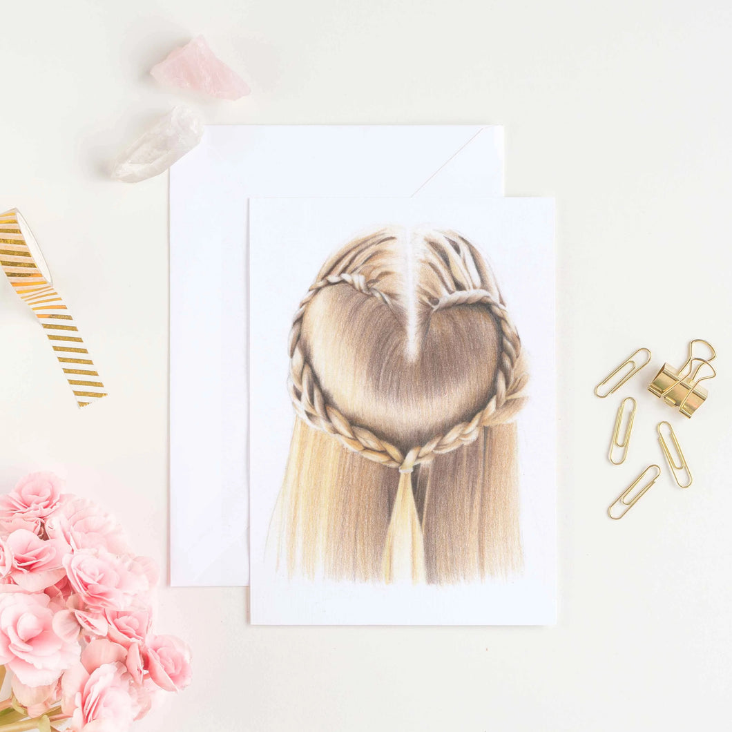 Image of print of girls hair in a love heart braid with flowers, clips and crystals next to it as a flat lay.