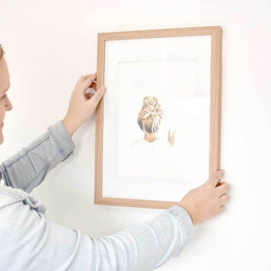 Image of artist putting original messy bun peace girl drawing in a frame on the wall.