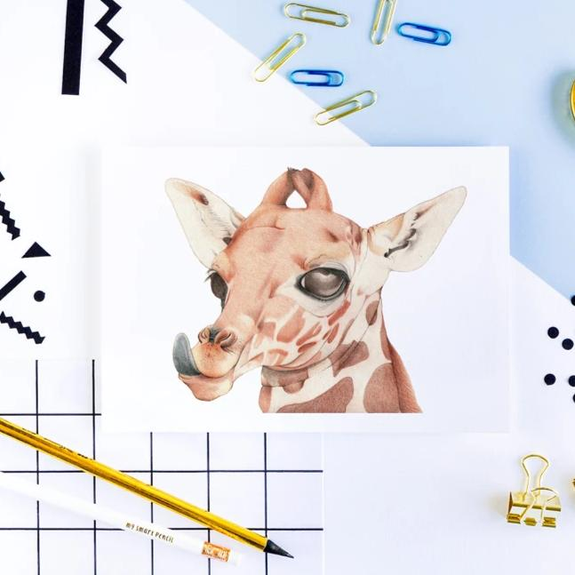 Image of print of giraffe head with a funky blue background with patterns, shapes and scattered pencils.