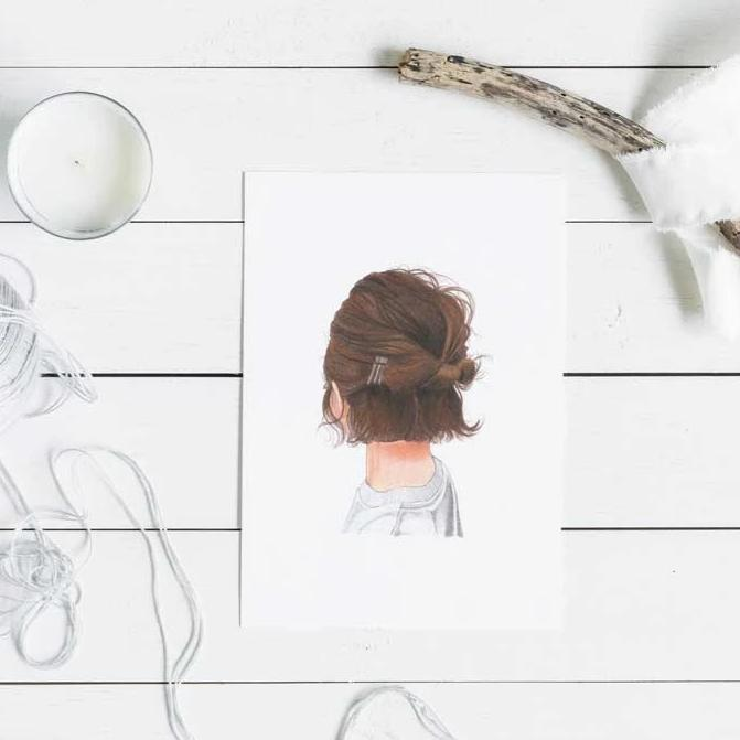 Image of brunette art print with a twig, candle and strong laying on white wood table.