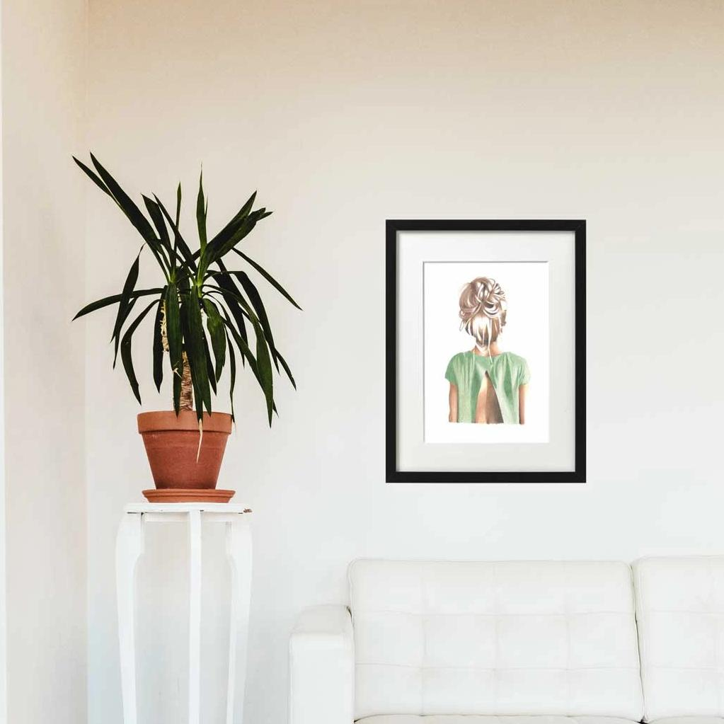 Image of back of girls head with bun and greet top hanging in a frame on a wall. Pot plant and couch in foreground.