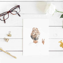 Load image into Gallery viewer, Image of art print of girl with messy bun hair with glasses, gold clips and white flower on a white wooden table.
