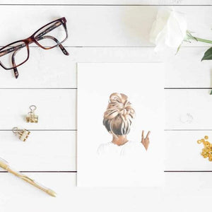 Image of art print of girl with messy bun hair with glasses, gold clips and white flower on a white wooden table.