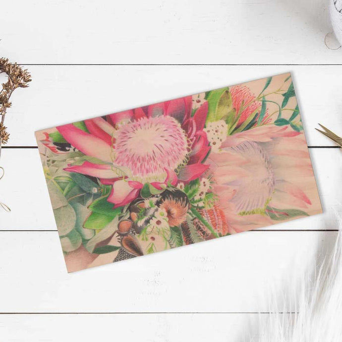 Image of wooden plaque with coloured pencil drawing of flowers on it, laying on a white wood table.