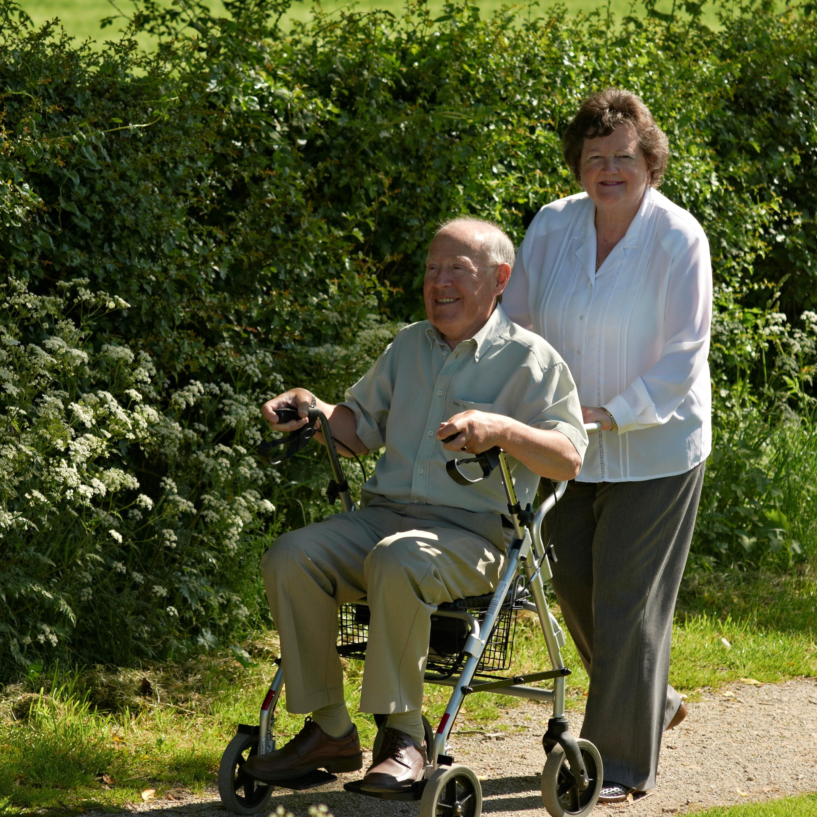 Two individuals walking outside, one sat on a rollator and the other pushing it.
