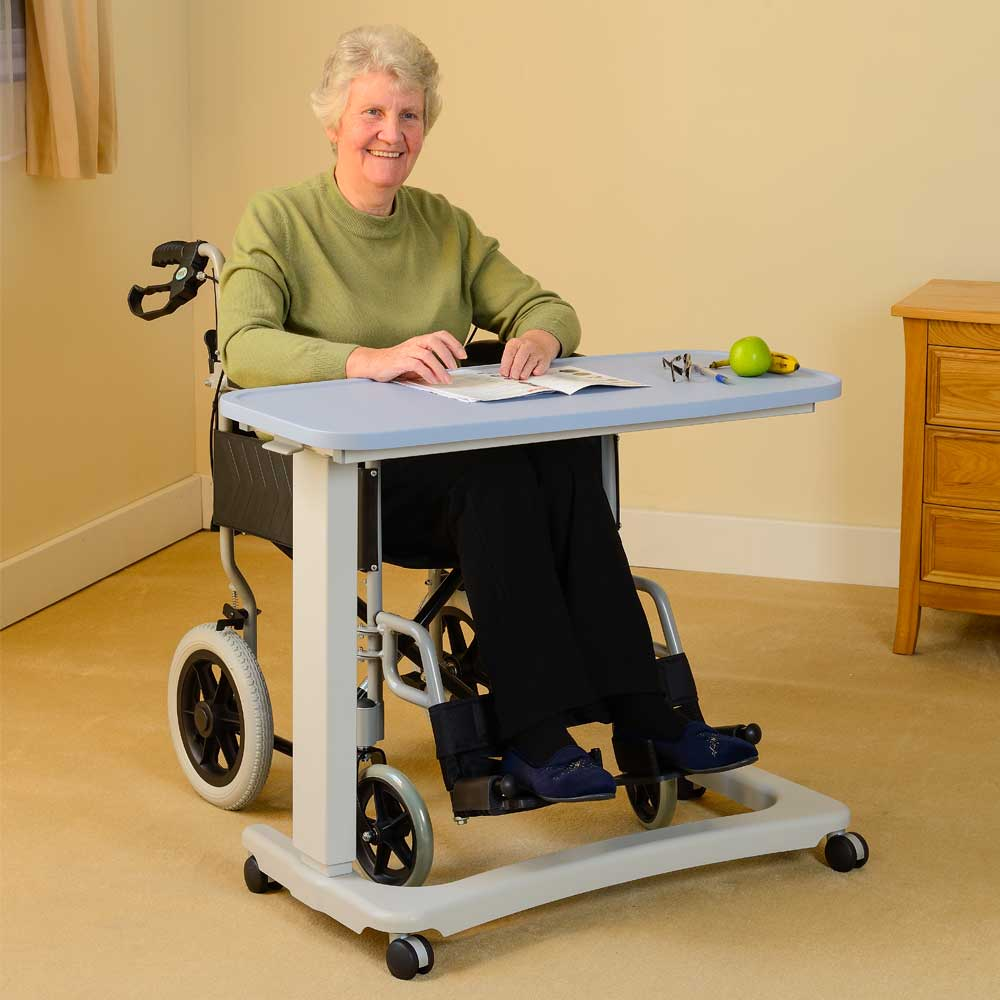 An individual in a wheelchair using a pale blue over-chair desk.
