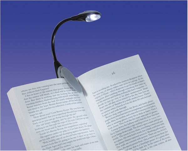 Book with L.E.D clip on light against blue background
