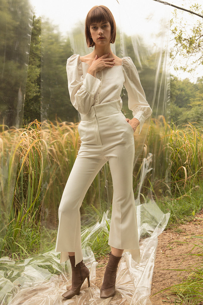 Slim flare trouser with front slits. High rise. Zip fly with hook-and-bar closure. Front slash pockets.