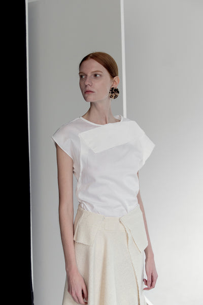 The Acre Top in white featuring cap sleeveless top with boat neckline, folded drape bodice detailing. Concealed zip down center back.