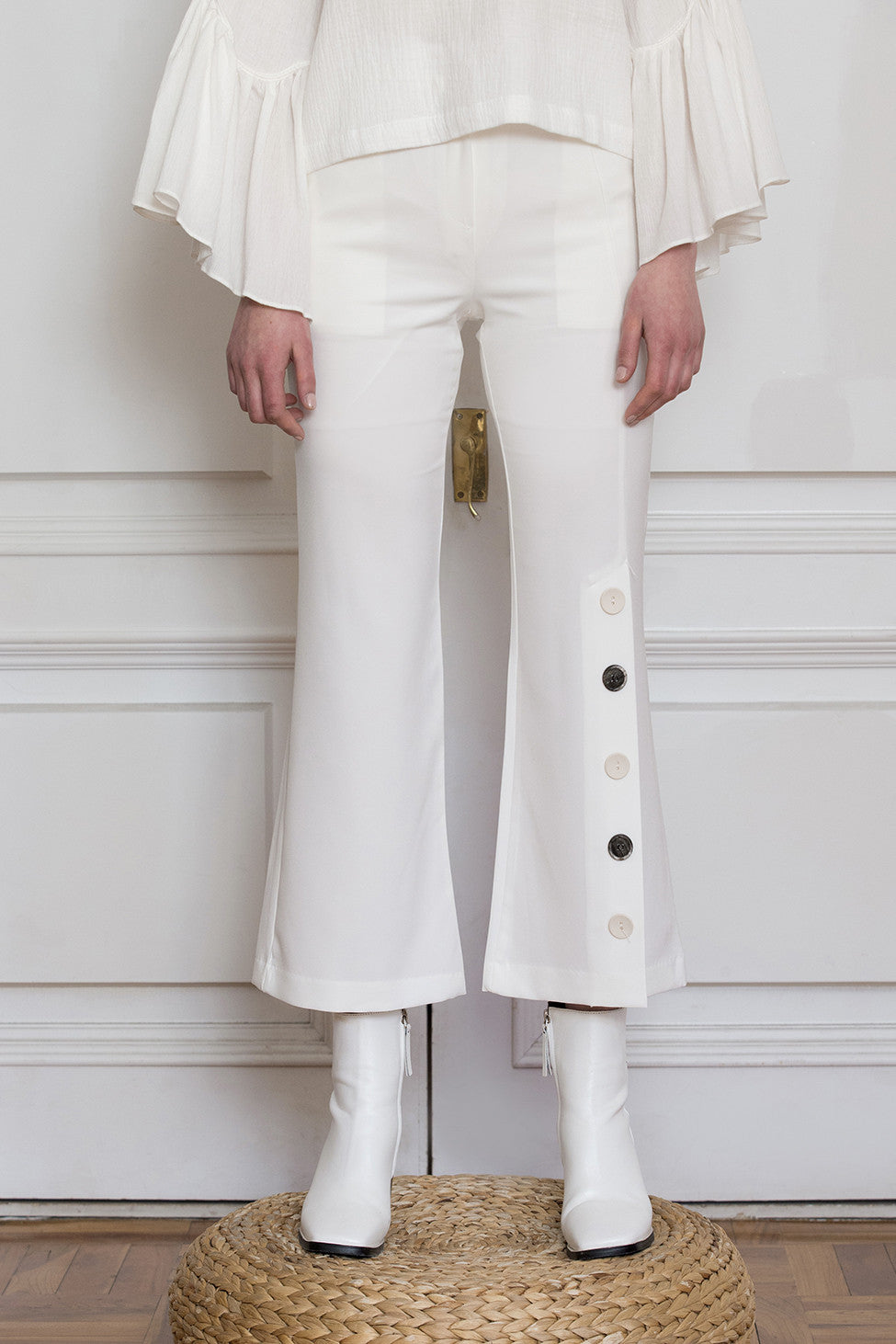 The Adalyn Pant in White featuring on-seam zip fly and hook closure, slanted front pockets, decorative button detail down left side. Partially lined. Cropped silhouette.