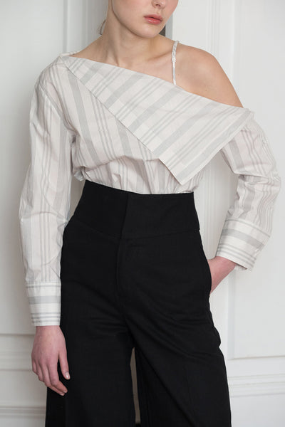 The Agate Top in White-and-Black stripe. Feature one-shoulder design with thin strap, asymmetric draped that sweeps across your décolletage and accentuates the collar. Button down closure along sleeves.