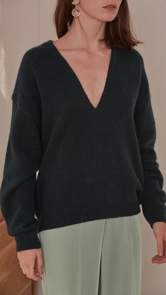 Agostina Sweater in Dark Green. Long sleeved pullover with deep v-neck in dark green lambs wool blend. Cowl neck ribbed sweater with pointed dropped shoulder seams and extra long sleeves. Designed to be loose fit.
