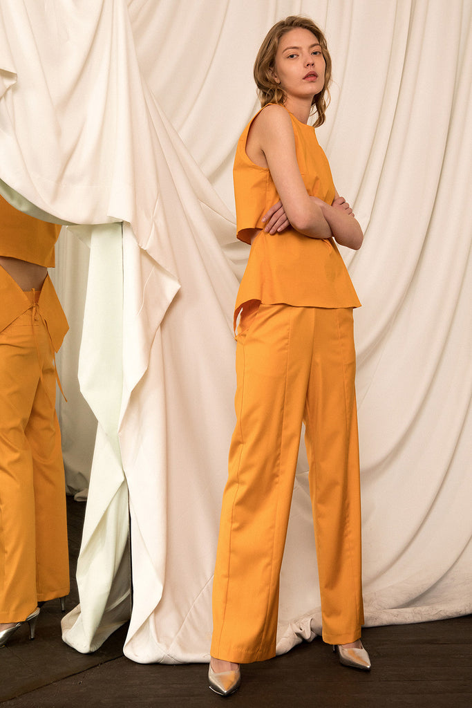 The Aisha Pant in Papaya, featuring slant two pockets, zip fly with hook-and-bar closure. High rise.