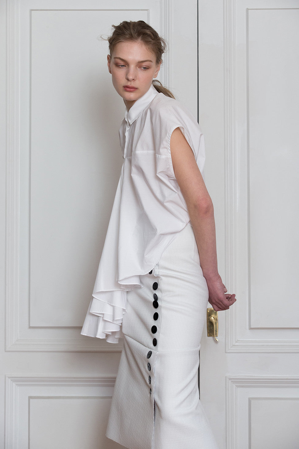 The Aletta Top in White featuring classic collar and asymmetric button down closure, cap sleeves, gathered flutter ruffle detailing.