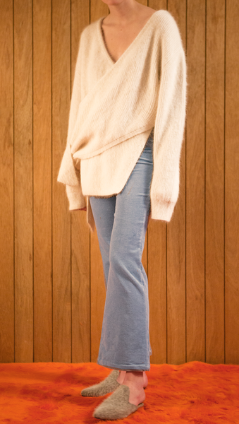 The Amuza Sweater in Ivory. Features chunky knit wrap-style sweater in dark brown alpaca and angora blend. Long sleeves, V-neckline (can be styled backward), self-tie wraps front around the waist, side slits. Pull on. Mid-weight. Oversized silhouette.