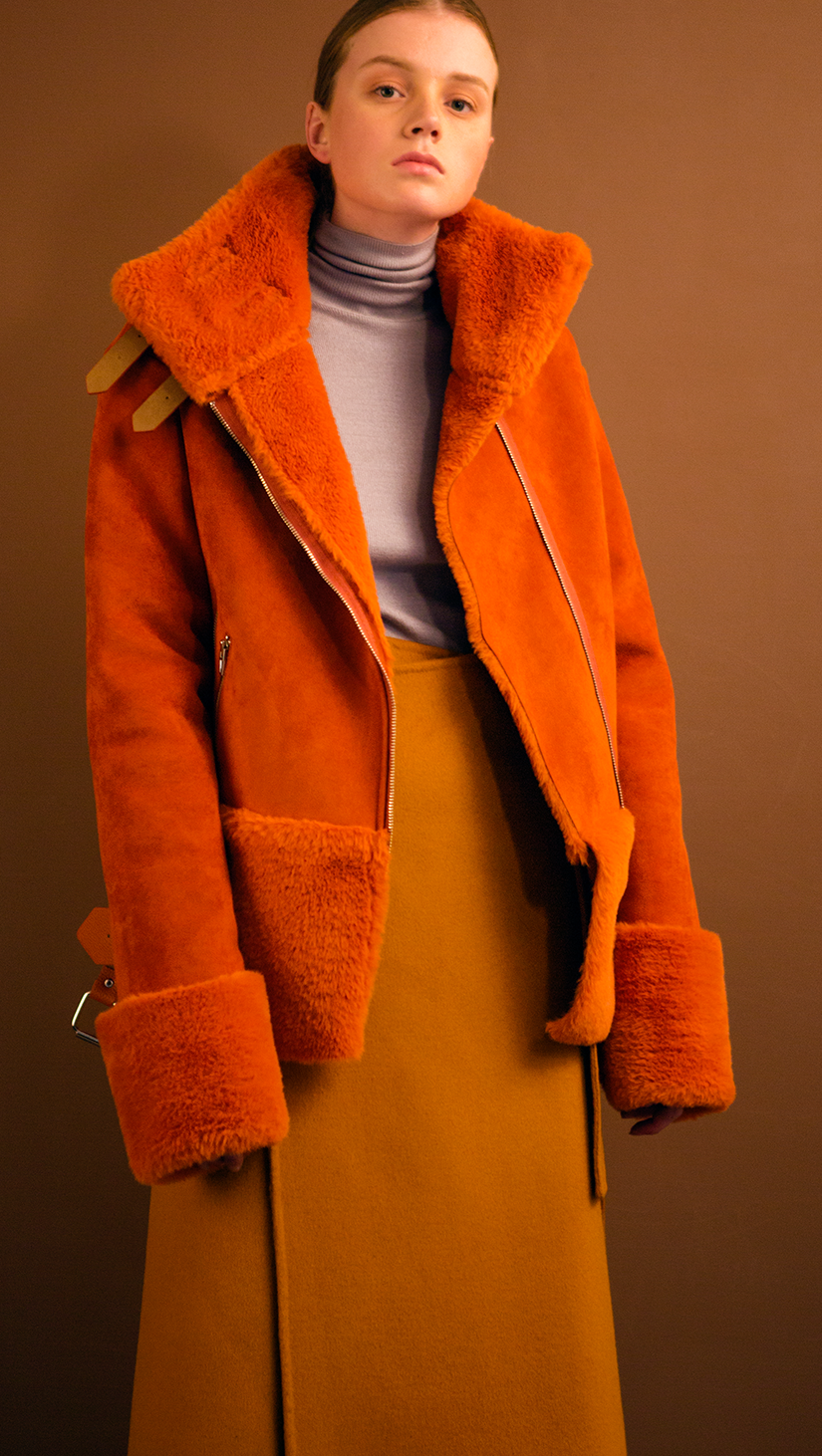 Moto-style suede shearling jacket fully lined in orange shearling. Super soft in suede, dropped shoulder, extra long sleeves with soft shearling detail at cuffs, front zip pockets, gusseted back panel, belt at waist with bucket closure, zip closure with attached wide belt in belt loops, Medium-weight. Fully lined. Oversized. Relaxed silhouette.