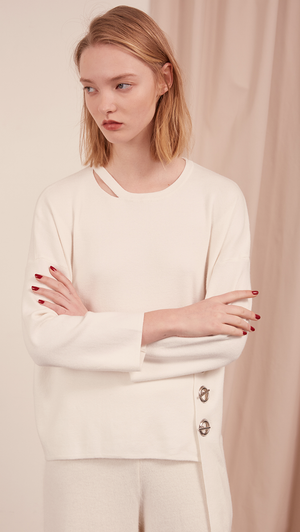 The Arie Sweater features round neck with cut out panel, asymmetric hem, back slit, sliver-tone hardware ring with hook closure. Pull on. Slightly relaxed fit.