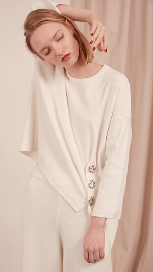 The Arie Sweater in off-white. Features round neck with cut out panel, asymmetric hem, back slit, sliver-tone hardware ring with hook closure. Pull on. Slightly relaxed fit.