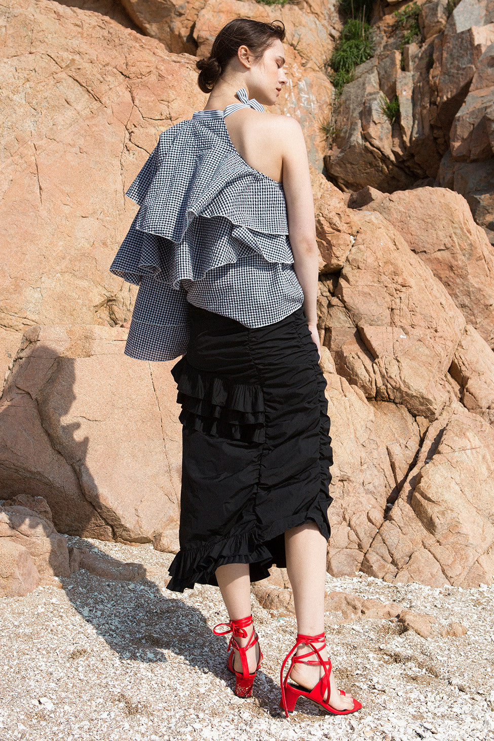 The Aurélie Skirt in Black featuring layered ruffles and cut on a bias. Asymmetrical hem. Concelaed side zip closure. Layered ruffles. Partial lined. High rise.